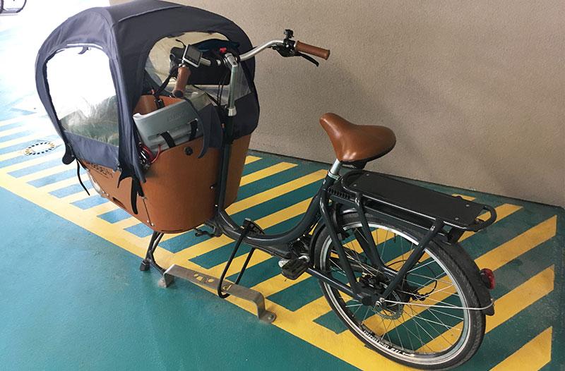 un vélo cargo accroché à un arceau de stationnement